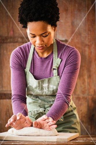 A young black woman kneading dough