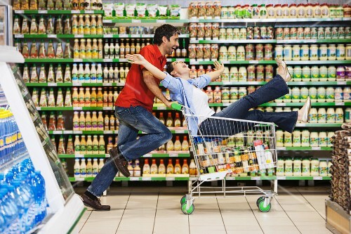 A man pushing a woman in a shopping trolley through the supermarket