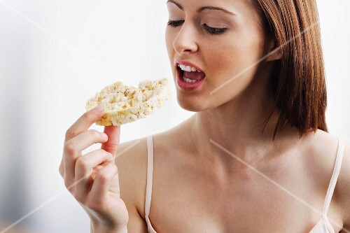 A young brunette woman biting into a rice cake