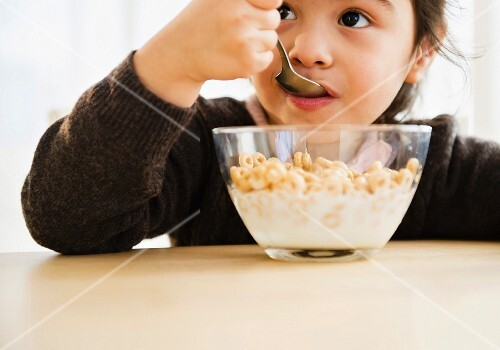 A little girl eating a bowl of cereal