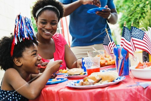 A black mother and her daughter eating at a table at a Fourth of July barbecue