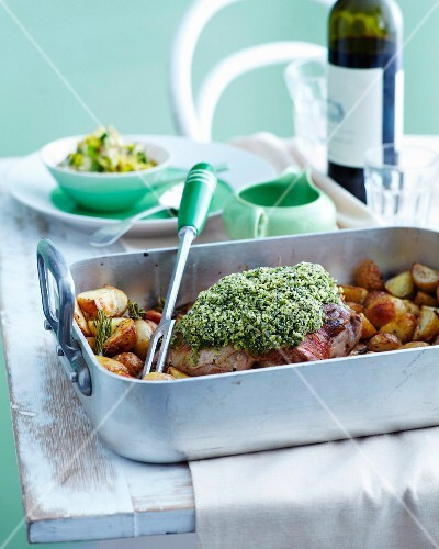 Roast lamb with a herb crust and potatoes in a roasting tin