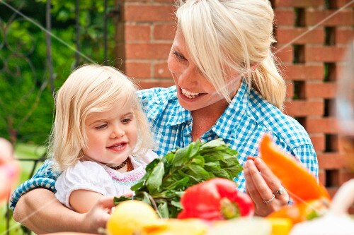 A mother and a toddler at a garden table with vegetables