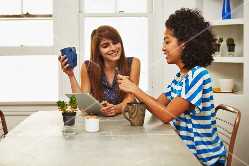 Two young women with a smartphone and a tablet PC in a kitchen drinking coffee