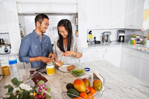 A young oriental couple making sandwiches in a kitchen