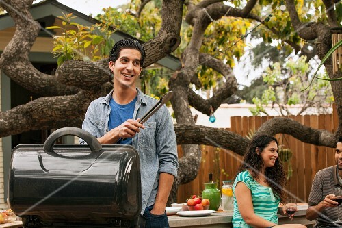 A young man standing at a barbecue holding a pair of tongs with a couple sitting in the background