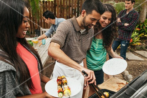 A man at a barbecue using tongs to give two women vegetable skewers