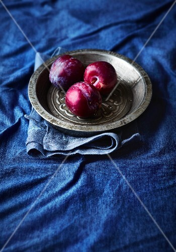 Three plums on a pewter plate on a blue cloth