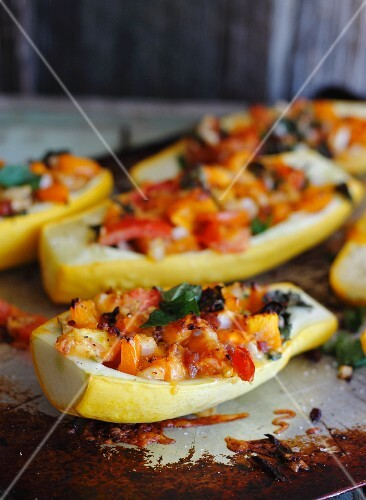 Yellow squash filled with vegetables on a baking tray