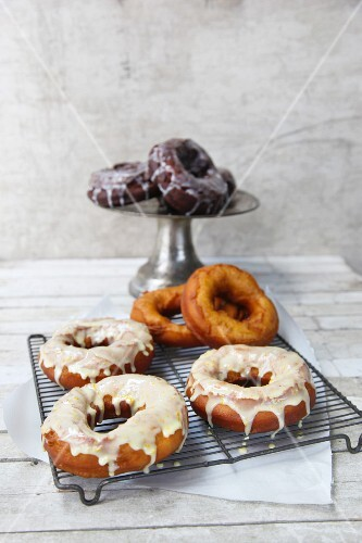 Glazed doughnuts on a wire rack and a cake stand