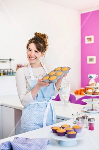 A woman holding a tray of homemade cupcakes