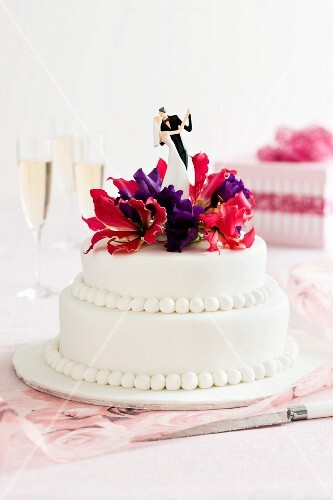 A wedding cake topped with a dancing bride and groom and flowers