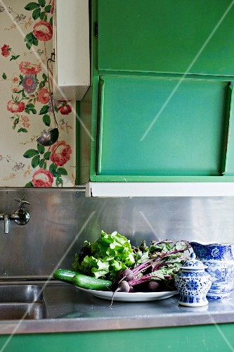 Fresh vegetables on plate next to blue and white crockery below green wall cabinet