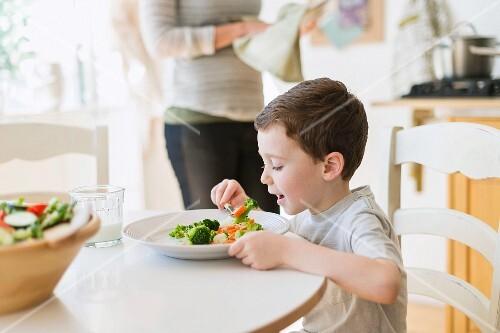 A little boy eating vegetables