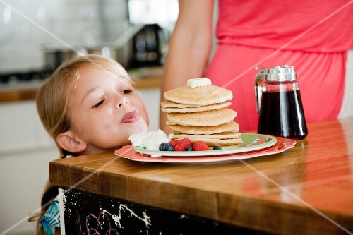 A mischievous little girl looking at pancakes on breakfast bar