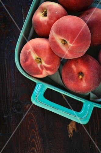 White peaches in a turquoise coloured baking dish