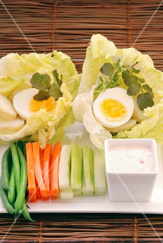 Vegetable sticks with a dip and hard-boiled eggs served on lettuce leaves