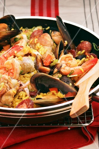 Paella with chicken, fish and seafood in a pan