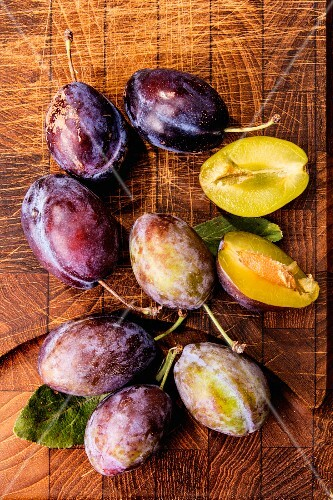 Fresh plums on a wooden board (seen from above)