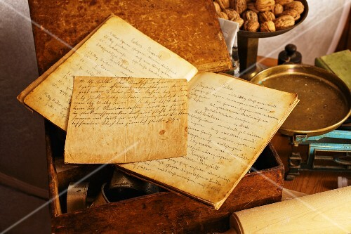 An old, handwritten recipe book with a pair of scales and walnuts