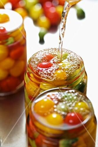 Tomatoes being preserved in jars