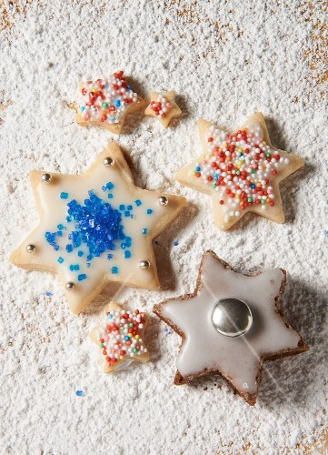 Various star biscuits on a sugared wooden board