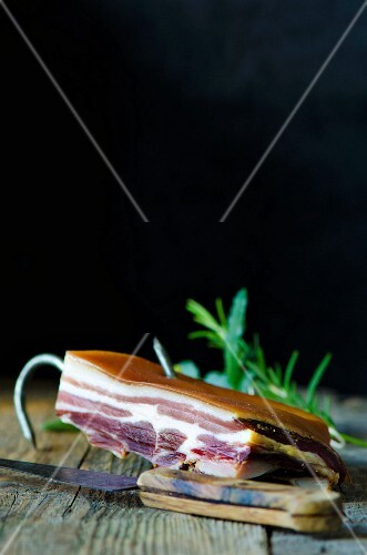 A slice of pancetta on a wooden board with rosemary and a knife