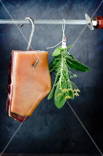 Pancetta hanging on a butcher's hook next to a bunch of fresh Italian herbs