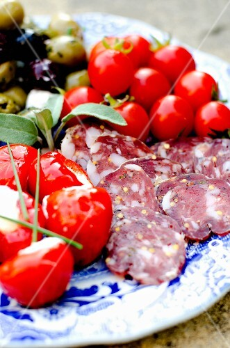 An antipasti platter with sliced salami, cherry tomatoes, pimientos filled with ricotta and olives