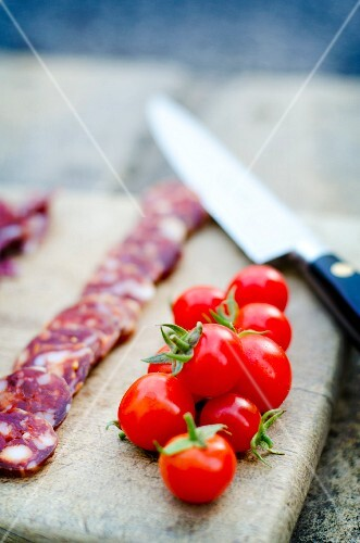 Chorizo slices on a wooden board with cherry tomatoes