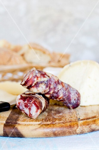 Italian salami and pecorino on a wooden board in front of a stone wall