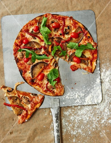 Vegetable pizza with tomatoes, aubergines and rocket, sliced