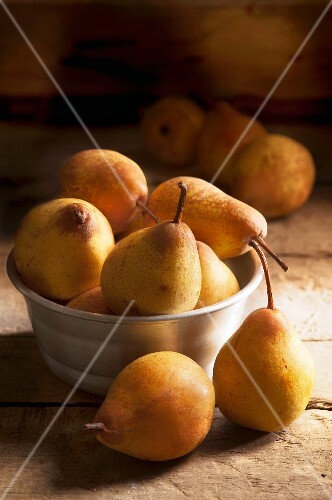 Pears in a metal bowl on a wooden surface