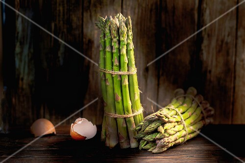 Bunches of green asparagus and eggshells