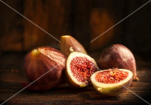 Fresh red figs, whole and halved, on a wooden table