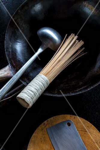 A ladle and a bamboo whisk in a wok with a meat cleaver on a chopping board next to it (Thailand)