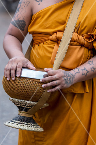 A Buddhist monk with a collecting bowl for offerings (Thailand)
