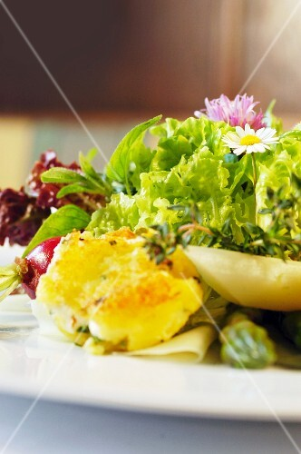 Mixed leaf salad with kohlrabi, garden herbs, asparagus tips, radishes and potato and sheep's cheese fritters (Austria)