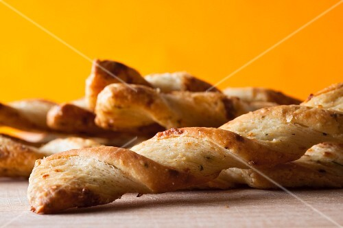 Parmesan breadsticks on a wooden board against an orange and yellow background