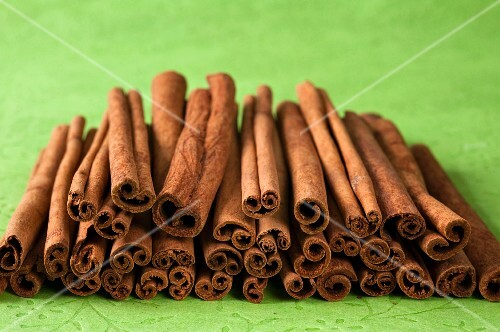 A stack of cinnamon sticks on a green surface