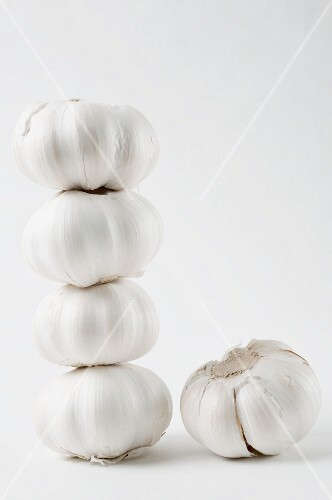 A stack of garlic bulbs and one next to it