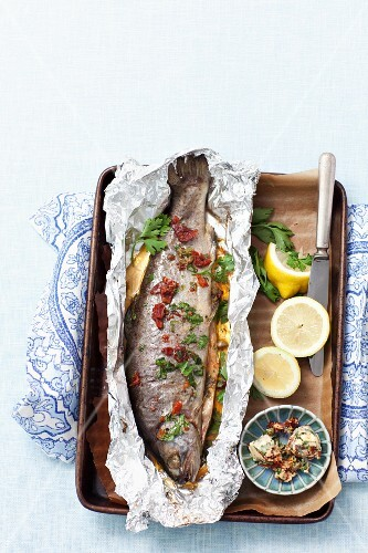 Baked trout with herbs and dried tomato butter