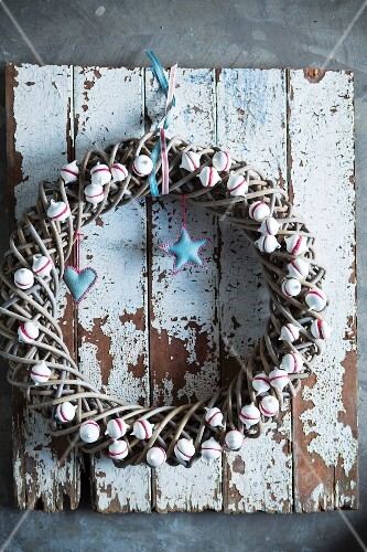 Festive wreath decorated with miniature meringues on wall