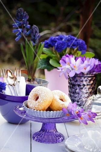 Donuts auf Tisch im Freien dekoriert mit Geschirr & Blumen in Lila-& Blautönen