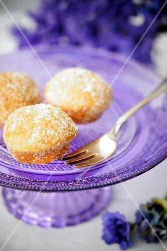 Drei Mini-Krapfen auf lilafarbenem Kuchenständer aus Glas