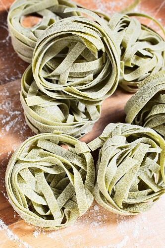 Spinach tagliatelle on a wooden surface