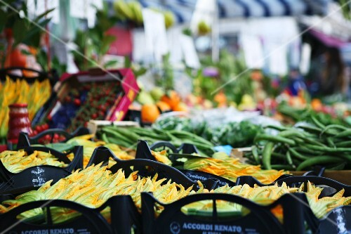 Fresh courgette flowers on a vegetable stand