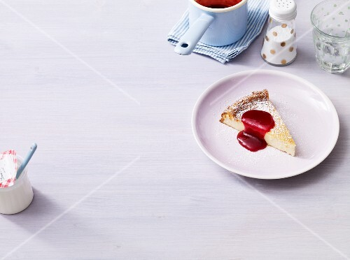 A slice of cheese cake with berry sauce