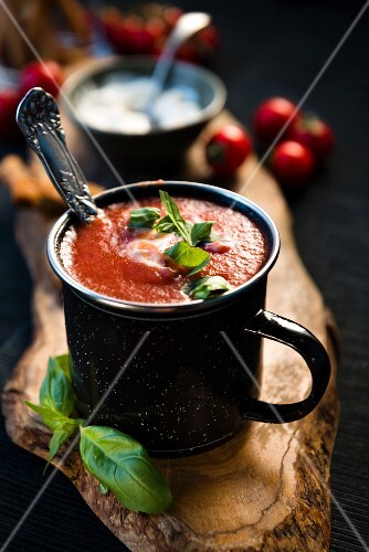 Tomato soup with grissini and fresh basil in an enamel mug