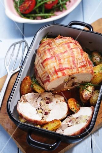 Stuffed turkey breast wrapped in bacon with roast potatoes
